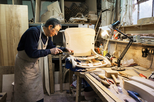 Man standing at a work bench in a carpentry workshop, working on a wooden chair with a small hand saの写真素材 [FYI02253124]