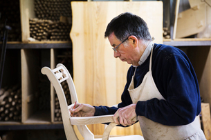 Man standing in a carpentry workshop, working on a wooden chair marking the armrest joint with a penの写真素材 [FYI02253127]