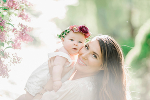 Portrait of a smiling mother and baby girl with a flower wreath on her head.の写真素材 [FYI02253128]