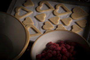 Valentine's Day baking. High angle view of a bowl of raspberries and heart shaped biscuits on a bakiの写真素材 [FYI02253132]