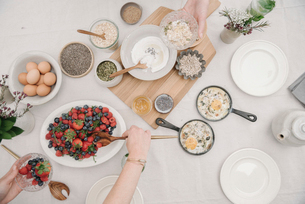 Overhead view of a table with food in dishes.  Breakfast, berries and yoghurt, eggs and bread.の写真素材 [FYI02253141]