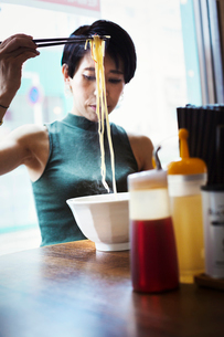 A ramen noodle cafe in a city.  A woman seated eating a ramen noodle dish using chopsticks.の写真素材 [FYI02253142]