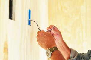 Senior man working on electrical wiring in a house.の写真素材 [FYI02253156]