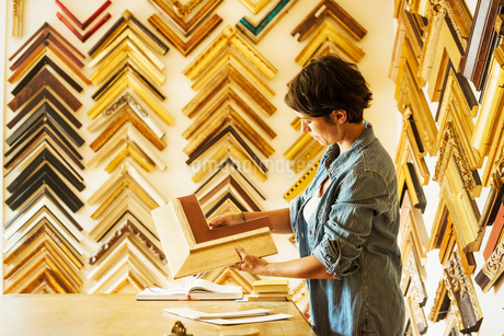 Woman working at a picture framers, a large selection of frames on the walls.の写真素材 [FYI02253170]