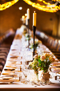 A wedding venue decorated for a party, with fairy lights and a long table set for dinner.の写真素材 [FYI02253172]