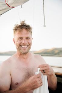 Smiling shirtless man standing on sail boat.の写真素材 [FYI02253189]
