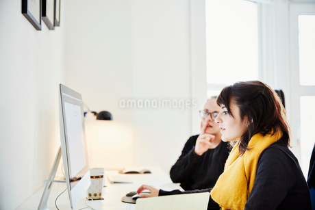 Two women seated sharing a computer screen and discussing the graphic content.の写真素材 [FYI02253200]