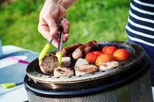 Woman preparing an English Breakfast on a camping stove.の写真素材 [FYI02253202]