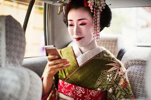 A woman dressed in the traditional geisha style, wearing a kimono and obi, with an elaborate hairstyの写真素材 [FYI02253213]