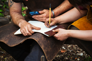 Man and woman, blacksmiths wearing aprons writing into a notebook sat in a garden.の写真素材 [FYI02253217]