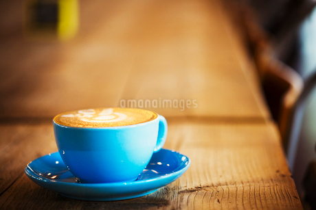 Specialist coffee shop. A blue china cup and saucer with frothy coffee.の写真素材 [FYI02253222]