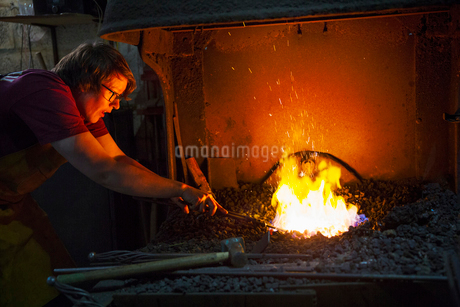 A blacksmith using tongs to heat something in a furnace.の写真素材 [FYI02253224]