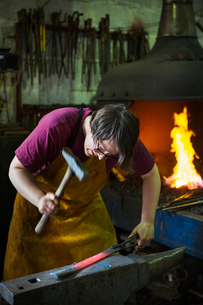 A blacksmith strikes a length of red hot metal on an anvil with a hammer in a workshop.の写真素材 [FYI02253236]