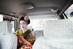 A woman dressed in the traditional geisha style, wearing a kimono with an elaborate hairstyle and flの写真素材 [FYI02253237]