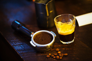 Specialist coffee shop. A coffee machine grounds holder, a heap of coffee beans and a glass cup withの写真素材 [FYI02253251]