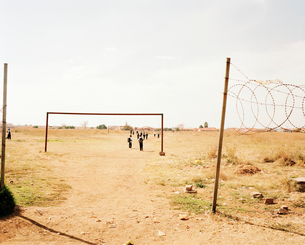 View across an arid common, barbed wire on a pole, group of children walking in the distance. Africaの写真素材 [FYI02253257]