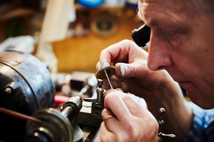A clock maker busy in his workshop.の写真素材 [FYI02253269]