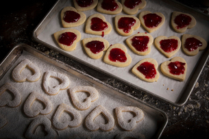 Valentine's Day baking, woman spreading raspberry jam on heart shaped biscuits.の写真素材 [FYI02253273]
