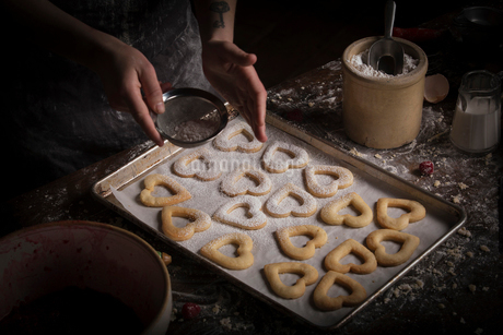 Valentine's Day baking, woman sprinkling icing sugar over heart shaped biscuits on a baking tray.の写真素材 [FYI02253320]