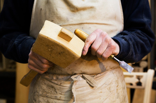 Close up of a man in a carpentry workshop, holding a wooden mallet and chisel.の写真素材 [FYI02253325]