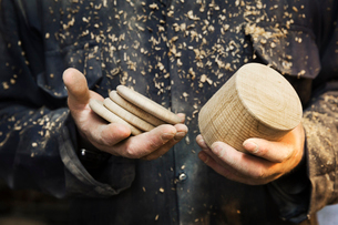 Close up of a man in a carpentry workshop, holding a wooden shape and wooden discs in his hands.の写真素材 [FYI02253330]