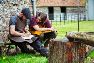 Two blacksmiths, a man and woman wearing aprons writing into a notebook sat in a garden.の写真素材 [FYI02253334]