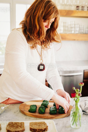 A woman preparing stuffed vine leaves as a lunch dish in a kitchen.の写真素材 [FYI02253337]