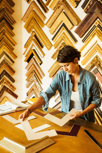 Woman working at a picture framers, a large selection of frames on the walls.の写真素材 [FYI02253343]