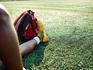 Boy wearing yellow sport shoe sitting on a lawn, a backpack at this feet.の写真素材 [FYI02253344]
