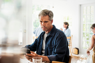 Man sitting in a coffee shop looking at his smart phone. Blurred foreground.の写真素材 [FYI02253355]