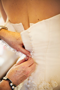 A woman buttoning the back of a bride's white wedding dress.の写真素材 [FYI02253357]