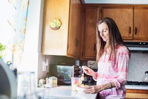 Senior woman standing in a kitchen, preparing food.の写真素材 [FYI02253376]