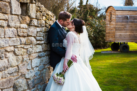 A bride and groom kissing on their wedding day standing in a garden.の写真素材 [FYI02253394]