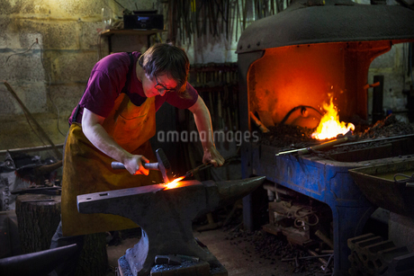 A blacksmith striking red hot metal on an anvil inside a workshop.の写真素材 [FYI02253401]