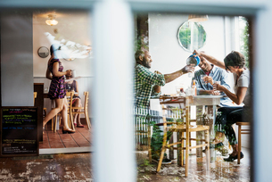 View through a window into a cafe, people sitting at tables.の写真素材 [FYI02253410]