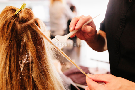 A hair colourist, a man using a paintbrush to cover sections of a woman's blonde hair.の写真素材 [FYI02253414]