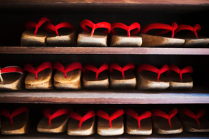 Rows of traditional wooden sandals with thick soles and red straps worn by geisha, okobo or geta.の写真素材 [FYI02253415]