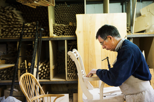 Man standing in a carpentry workshop, working on a wooden chair marking the armrest joint with a penの写真素材 [FYI02253416]