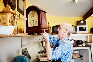 A clock maker displaying his work on a shelf in his workshop.の写真素材 [FYI02253448]