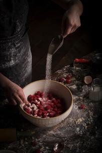 Valentine's Day baking, woman preparing fresh raspberries in a bowl, adding sugar.の写真素材 [FYI02253449]