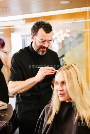 A hair colourist, a man using a paintbrush to cover sections of a woman's blonde hair.の写真素材 [FYI02253452]
