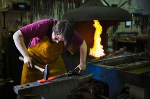 A blacksmith strikes a length of red hot metal on an anvil with a hammer in a workshop.の写真素材 [FYI02253457]