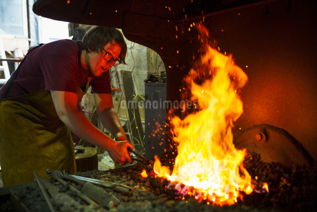 A blacksmith using tongs heats something in a furnace.の写真素材 [FYI02253471]