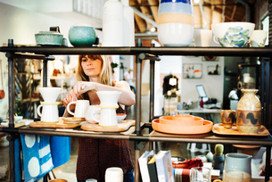 Woman standing in a shop, arranging ceramic objects on a shelf.の写真素材 [FYI02253472]