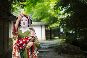 A woman dressed in the traditional geisha style, wearing a kimono and obi, with an elaborate hairstyの写真素材 [FYI02253473]