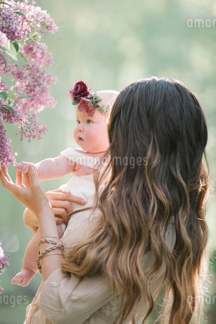 Mother holding baby girl with a flower wreath on her head.の写真素材 [FYI02253476]