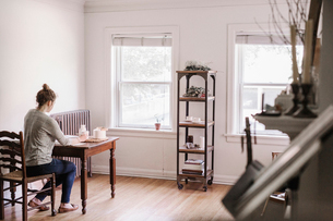 Woman sitting at a table in her apartment, writing in a diary, morning routine.の写真素材 [FYI02253496]