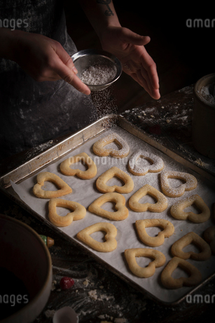 Valentine's Day baking, woman sprinkling icing sugar over heart shaped biscuits on a baking tray.の写真素材 [FYI02253498]