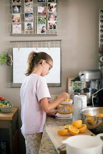 Family preparing breakfast in a kitchen, girl squeezing oranges.の写真素材 [FYI02253505]