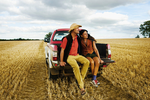 A man in a straw hat and a woman sitting in the back of a pick up truck.の写真素材 [FYI02253525]